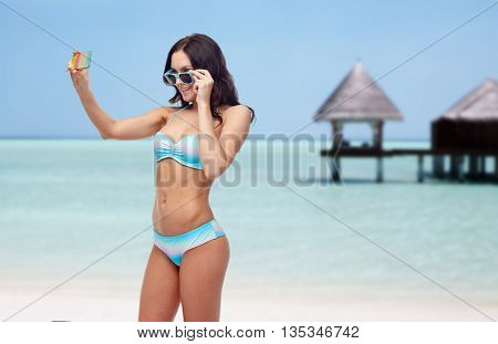 people, technology, summer and travel concept - happy young woman in bikini swimsuit and sunglasses taking selfie with smatphone over maldives beach with bungalow background