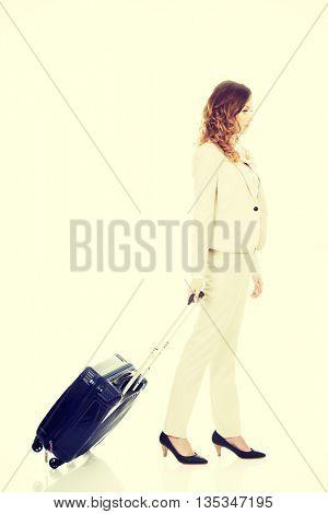 Businesswoman dragging suitcase.