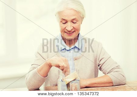 savings, money, annuity insurance, retirement and people concept - smiling senior woman putting bank notes into glass jar at home