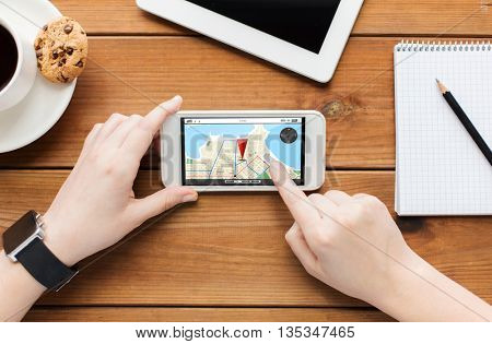 technology, business, people and navigation concept - close up of woman with gps navigator map on smartphone screen and coffee cup on wooden table