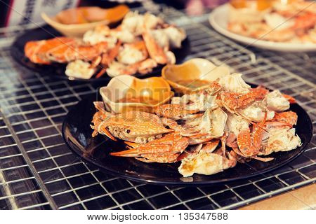 cooking, asian kitchen, sale and food concept - crabs dish at street market