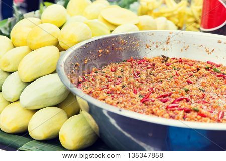 cooking, asian kitchen, sale and food concept - chilly wok or pilaf and mango at street market