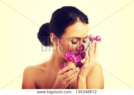Topless woman with purple orchid branch