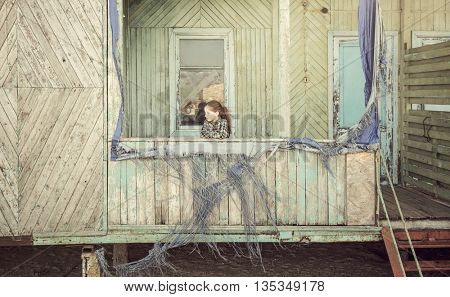 beautiful little girl standing on porch of abandoned wooden cabin