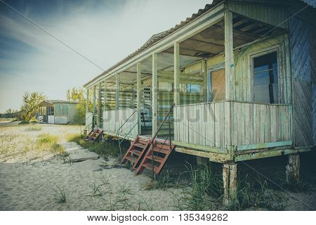 view on porch of old abandoned wooden cabin at a seaside