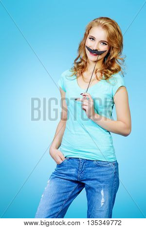 Cute cheerful girl holding fake mustache on a stick and smiling. Studio shot.