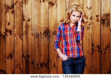 Pretty blonde girl in checkered shirt and jeans standing by a wooden wall. Youth style, fashion.