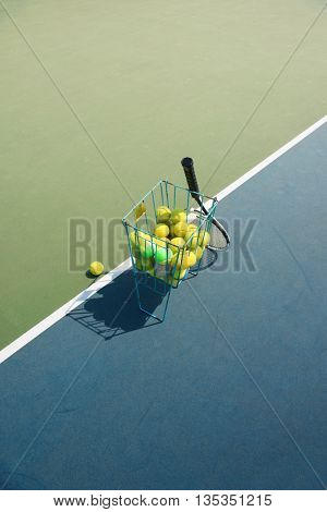 Tennis court with tennis balls in tennis ball basket stand with natural shadows. Intentionally shot in surreal tone.