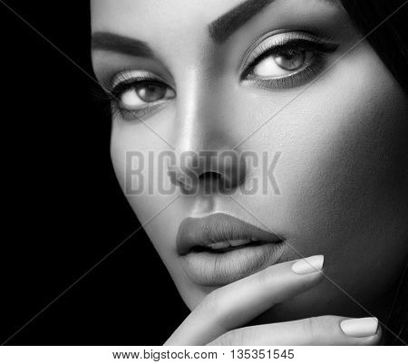 Beauty fashion black and white woman face portrait with perfect makeup and nails isolated on black background. Beauty girl face close up