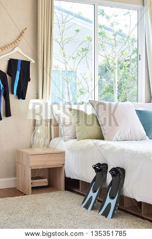 Stylish Bedroom Interior Design With Colorful Pillows, Blue Flippers And Decorative Table Lamp.