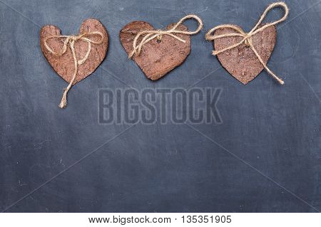 Three (3) decorative hearts made from tree bark on chalkboard, positioned above the middle of the photo. Hearts decorated with eco twine. Eco decor. St. Valentines greeting card idea. Handmade design.