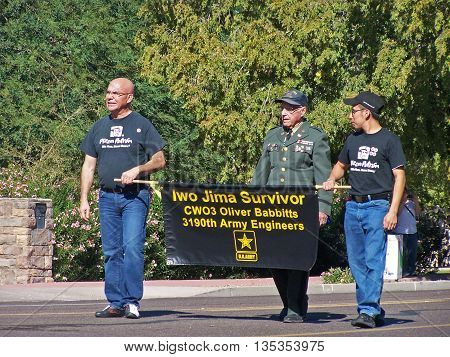 PHOENIX, AZ- NOV. 11: Iwo Jima Survivor walking with two escorts holding banner in Veteran's Day Parade in Phoenix, AZ on November 11, 2013.