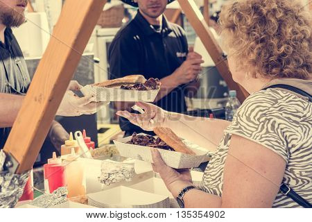 Customer receiving serving at food stand. Street food photography.