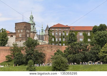 KRAKOW POLAND - JUNE 17 2013 : View on Wawel Royal Castle and Vistula boulevards. Place often visited by tourists and locals for purposes of relaxation on sunny days.