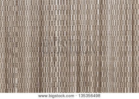 abstract vertical pattern of a cover from wooden straws for the textured background and for wallpaper of sepia color