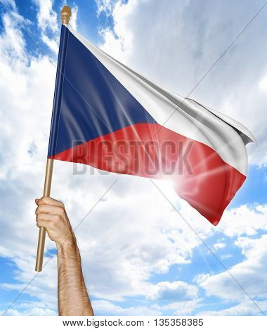 Person's hand holding the Czech Republic national flag and waving it in the sky, 3D rendering
