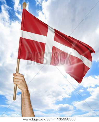 Person's hand holding the Danish national flag and waving it in the sky, 3D rendering