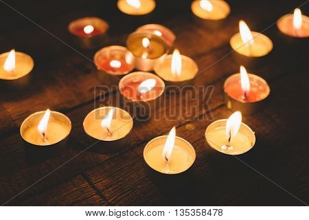 Group of lit candles in the night, on wooden plank background