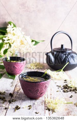 Healthy medicine green tea with elder flower in pink cast iron cup on old white wooden table with elder flower branches. Copy space.