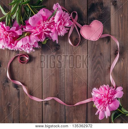 Peony flowers on old wooden boards, frame for message