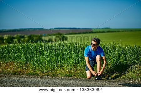 man runner athlete warming up before jogging along a green field in the early morning. man lunged forward on one knee. man fitness sunset jogging workout wellness concept. free space in front of the person