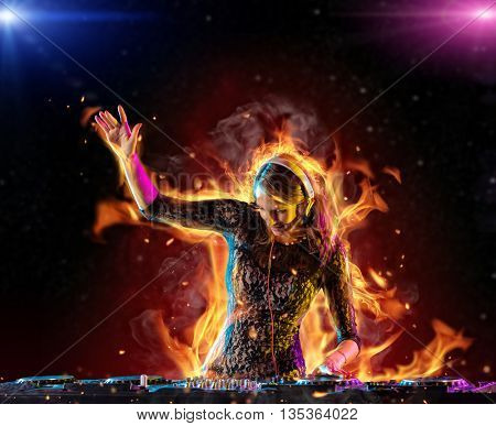 Disc jockey brunette girl mixing electronic music with fire flames around
