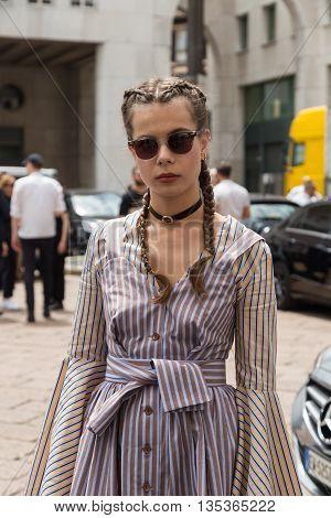 MILAN ITALY - JUNE 19: Fashionable woman poses outside Ferragamo fashion show building during Milan Men's Fashion Week on JUNE 19 2016 in Milan.