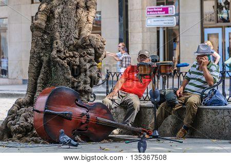 HAVANA, CUBA - MARCH 16, 2016: Musicians relaxing in Plaza de las Armas in the Old Havana neighborhood Cuba