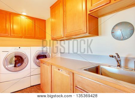 Laundry Room With Modern Appliances And Light Tone Cabinets.