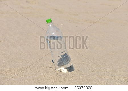 Ice Cold Unlabelled Bottle Of Refreshing Water Standing Upright In The Golden Sand On A Tropical Bea