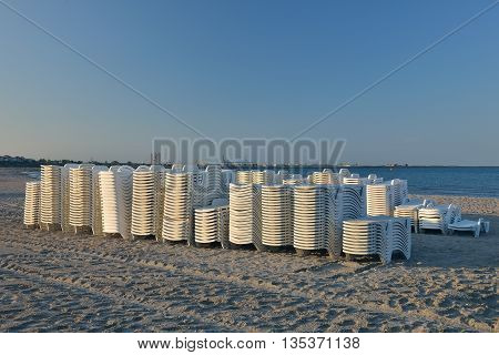 Sunbeds On The Beach Stacked, Ready To Be Put On The Beach To Enjoy The Tourists Of The Sun And Good