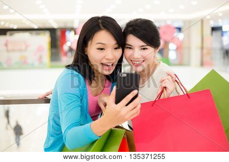 Young woman holding many shopping bag and taking photo together