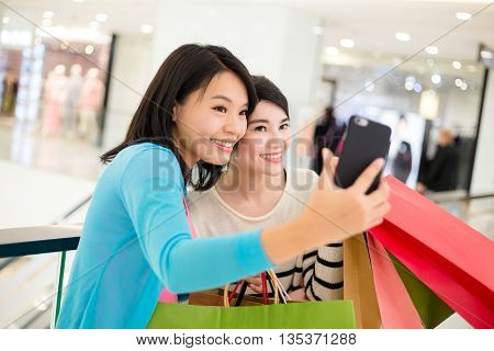Two woman holding shopping bag and taking photo together