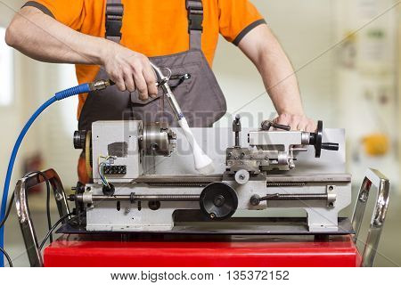 Machinist working a metal lathe on the workbench