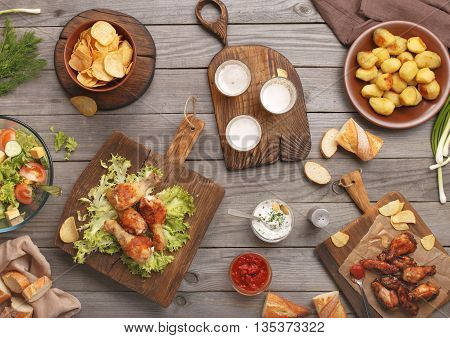 Outdoors Food Concept. On the wooden table different food grilled chicken legs buffalo wings bread salad potatoes potato chips and beer top view