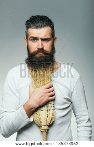 Bearded man with serious sad face in white shirt holding broom as beard in studio on grey background