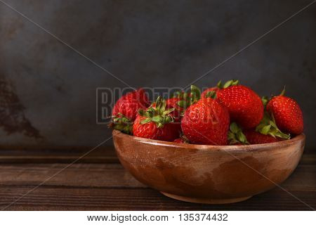 Horizontal still life of a bowl full of fresh picked strawberries on a wood table. Horizontal format with copy space.
