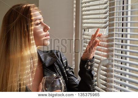 serious girl with wineglass looking through blinds