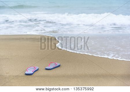 Flip-flops on the beach on sea background.