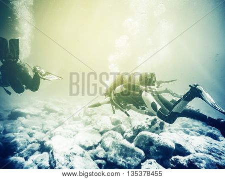 People doing scuba diving underwater close to the sea floor. Vintage tone.