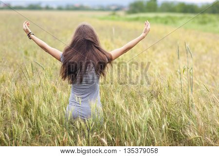 Young woman with long brown hair standing in wheat field raising hands. Unity with nature concept.