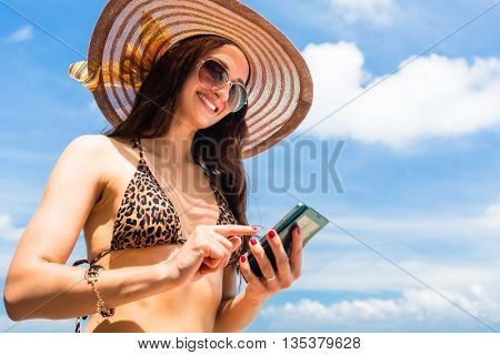 Woman on beach with phone typing text message or chatting