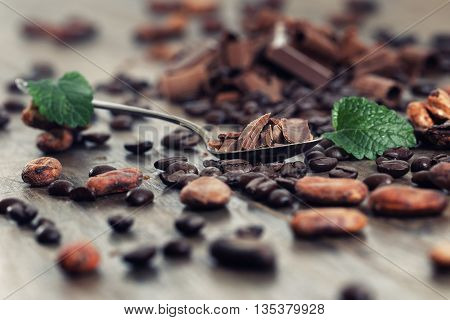 Dark chocolate pieces, cocoa powder and coffee beans on a wooden table