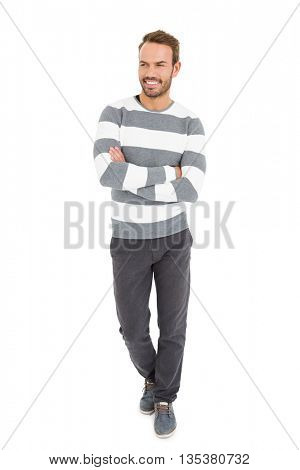 Happy young man in winter wear standing with arms crossed on white background