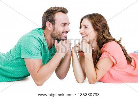 Happy young couple lying on floor looking to each other on white background