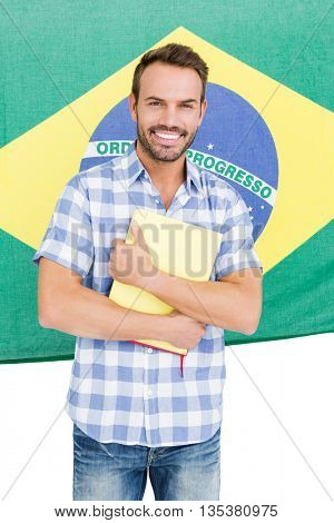 Portrait of happy young man standing with folder in front of brazilian flag