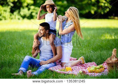 Beautiful cheerful faimly outdoors enjoying picnic outing
