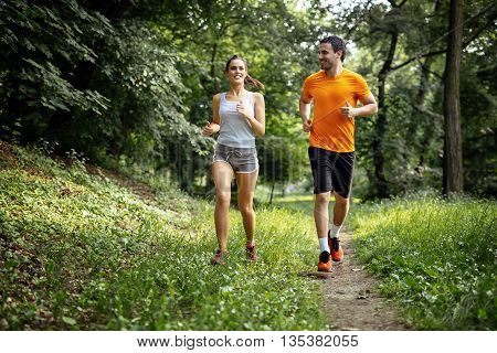 Healthy couple jogging in nature in good spirit
