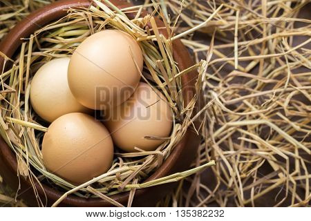 Eggs in wooden bowl on rice straw background