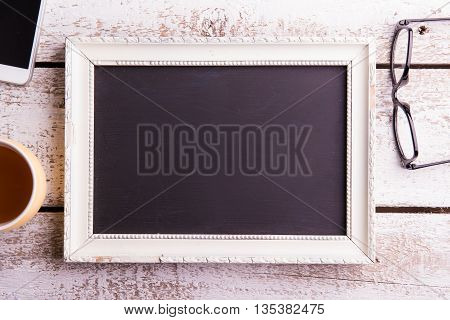 Empty Picture Frame, Eyeglasses, Cup Of Coffee And Smartphone